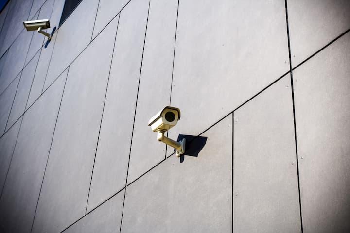 Duas câmeras de rua, apontadas em lados opostos, anexadas a um prédio.